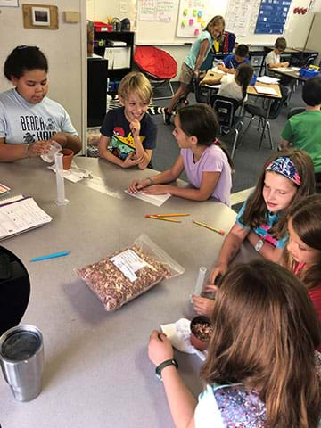 A group of elementary school students works at a table to design drought-resistant soil.