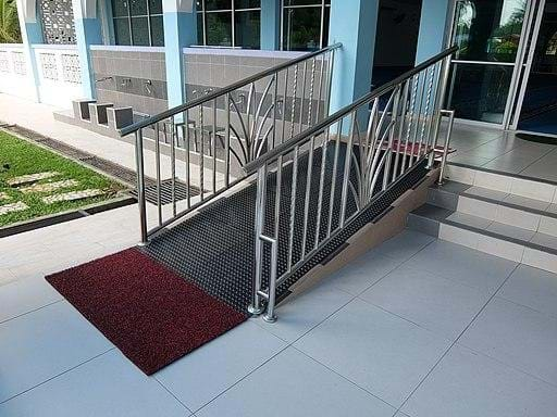 Image of a small wheelchair ramp on an incline leading up to the front doors of a building.