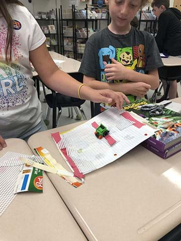 Two students test elements of friction using a green toy car, and an inclined ramp set up on a textbook.