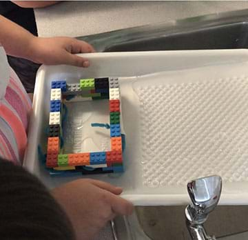 The photo shows a paint tray holding a house made of plastic bricks. Water is flowing into the tray. The plastic house has pipe cleaners and tape protruding from two windows.