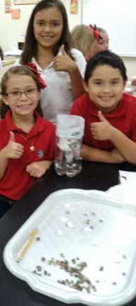 A photograph shows three young students holding their thumbs up in front of their water filtration system.