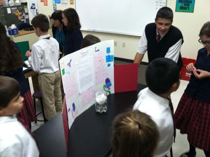 A photograph shows numerous youngsters milling around a classroom table on which sits a student-made water filter and a poster that explains the water filtration process.