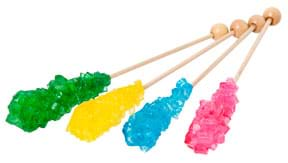 A photograph shows four wooden skewers, each with a cluster of jagged colored crystals at one end: green, yellow, blue and red.