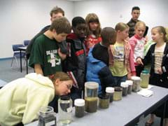 Photo shows nine kids examining 11 jars of clear and murky liquids lined up on a table.