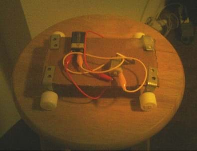 Photo shows a model vehicle made with cardboard, L-brackets, wires, alligator clips, a 9-volt battery, and wheels.