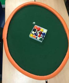 "A photograph shows a view from above an elliptical-shaped pool table with a set of pool balls on a green surface material with a curved orange foam ""curb"" border around its perimeter."