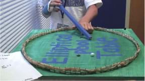 A photograph shows a student using a blue wooden stick as a cue stick to move a white marble on an elliptical pool table that is a painted wooden board enclosed by a fence (bumper edges) of rubber bands stretched on a ring of nails pounded into the perimeter.