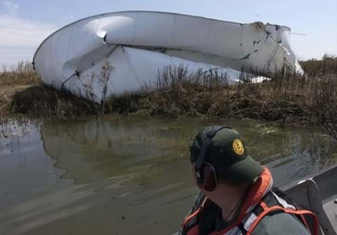 Photo shows a man in a small boat looking at a large mangled pile of white steel (a ruptured above-ground oil storage tank) in a marshy area.