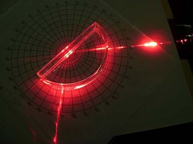 A photograph from above shows a red beam of light from a laser pointer laying on a tabletop shining at and being reflected away at a different angle from a semi-circular hollow block that sits centered over a polar graph.