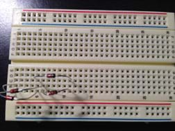 A photograph shows the wires of four diodes inserted into various holes in a plastic breadboard.