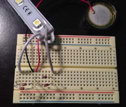 The same breadboard as Figure 3, now with an LED light bar connected via two wires.