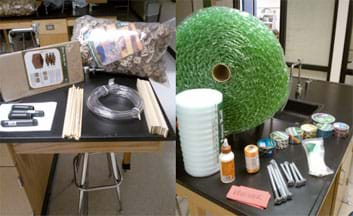 Two photographs: On a table are a package of cardboard interlocking packing pieces, a moving glass divider kit, a coiled length of clear vinyl tubing, a handful of 16-inch wooden dowels, a handful of wooden flat sticks, two 4-inch and two 6-inch pieces of black PVC pipe. On the barter table are roll of bubble wrap, roll of white plastic packing foam, bottle of wood glue, roll of orange polypro twine, six rolls of patterned/colored duct tape, roll of silver duct tape, package of white plastic zip ties, four 8-inch and four 5-inch silver screw bolts, along with a stack of paper vouchers.