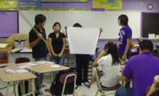 Photo shows four students standing in front of a class, holding a large map and making a presentation.