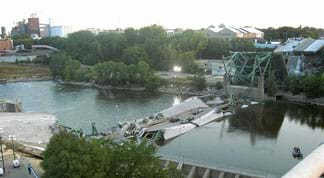 A photograph shows the scene at the I-35W Mississippi River Bridge after its August 2007 collapse. The bridge deck is in the water with a few cars on it, broken off from the rest of its steel truss components at the river's edge.