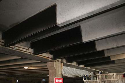 A photograph of the concrete ceiling of a parking garage shows an example of concrete structures being strengthened by CFRP reinforcement in the form of a three-sided wrap of six beams.
