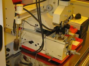A photograph shows a mechanical device—the Carl Suss Mask Aligner MJB3—which is used to print research project circuits using ultraviolet light.