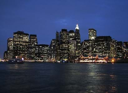 A view of Manhattan at night probably from boat.  Buildings and port structures are brightly lit.
