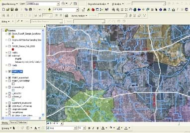An image from ESRI's ArcGIS® software with a table of contents on the left that gives layers that can be turned on and off, a top screen space that has many different icons for GIS manipulation tools, and a main screen on the right and center that displays aerial photos and GIS layers on top of them.