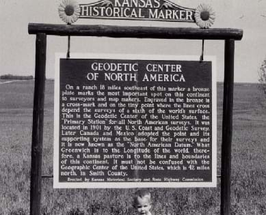 "A black and white photograph displays a hanging sign in front of a an empty field. The post holding the sign reads ""Kansas Historical Marker,"" and the main sign reads ""Geodetic Center of North America."""