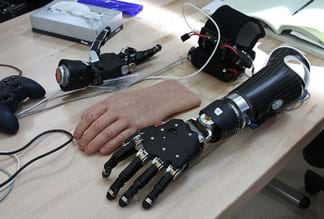 A photograph shows an assortment of parts and wires on a tabletop, including a black and silver robotic-looking forearm and hand as well as a covering for the hand that looks convincingly like a real human hand (skin, nails wrinkles, hair).