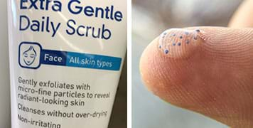 "Two photographs. A close-up of the label for a tube of ""extra gentle daily scrub"" for face and all skin types. Further, it says: Gently exfoliates with micro-fine particles to reveal radiant-looking skin. A close-up photograph shows the tip of a finger with a blob of clear gel containing a scattering of tiny round blue particles—plastic microbeads."