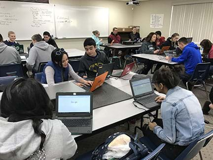 A high school classroom, with four groups with four to five students in each group, each student is working at a laptop computer, actively engaged working.