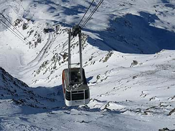 A photograph shows an aerial tram ascending above a snow-covered, rocky mountain. Far below in the distance is a docking building.