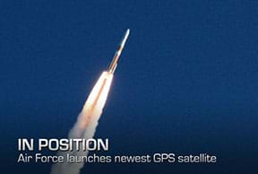 "A photograph shows a blasting off rocket (equipped with a GPS satellite) as it propels through the air, trailing a stream of flame and smoke from the engines. The rocket is red on top and white on bottom with a red stripe in the middle. Overlaid text reads ""IN POSITION. Air Force launches newest GPS satellite."""