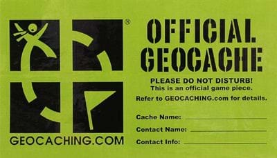 A photograph shows a rectangular green label with black lettering and the official geocache URL (geocaching.com) and logo/emblem—a cartoon of a person tracking towards a waypoint flag, searching for a hidden treasure. Blank lines prompt the user to fill in the cache name, contact name, and contact info.