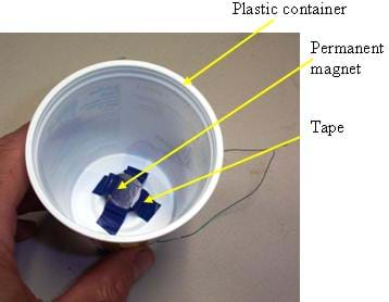 Photo shows a small permanent magnet attached to the inside of a plastic cup with electrical tape.