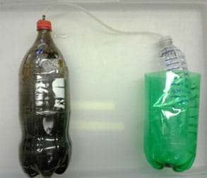 A photograph shows a capped 2-liter bottle on the left with a tube connecting to a capped, open-bottom container floating in a container of water on the right.