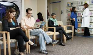 Photo shows four adults sitting and reading in chairs in a medical office waiting room, while in the background a woman in a lab coat talks to another person.