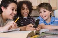 Photo shows three boys at a table with books and pencils, laughing at something they can all see on a cell phone screen.