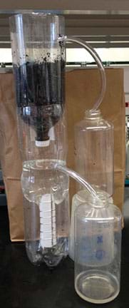 A photo shows a contraption made of three tall plastic bottles stacked on top of each other. The lowest bottle has no neck and provides a base to hold the middle one (also with no neck), which has a clear tube inserted into its side. The top bottle is inverted with its narrow neck and cap pointing down into the middle bottle; it is half-filled with a black substance; a clear tube is inserted into the high part of its wall. The two tubes each run into the openings of two other clear bottles, one of which is elevated on a plastic platform so viewing it is not blocked by the other bottle receiving a tube.