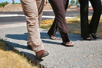 A photograph shows the legs and feet of three people walking on a gray sidewalk that looks like it is made of much aggregate, as spaces can be seen between the aggregate pieces.
