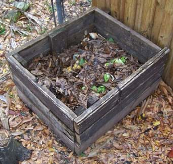 A photograph shows an open box made of boards sitting next to a fence outdoors, and partially filled with food scraps and leaves.