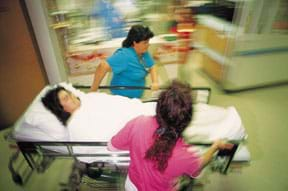 Photo shows two running hospital workers wheeling a woman on a gurney down a hallway.