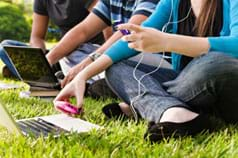 Photo shows three teenagers sitting on the grass using laptops and cell phones and listening to music with ear buds.