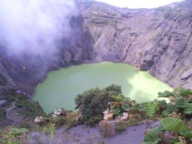 Photo shows a muddy green lake surrounded by steep rocky banks.
