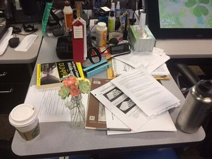A photograph shows a teacher's classroom desk cluttered with many objects—papers, books, coffee cup, water bottle, pencils, pens, Kleenex box, vitamin bottle, lotion bottle, camera, awards, sunscreen bottle, stapler, paperclips, picture frame, flowers, etc.