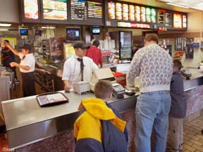 A photograph shows the inside of a fast food restaurant, with a man and two boys at the counter and employees working behind the counter.