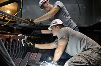 Two men in pants, t-shirts, hardhats and gloves use their hands to work on a large device; they are fixing a generator at a power plant.