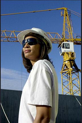 A photograph shows a woman wearing a hard hat and wrapped sun glasses at a construction site with a crane in the background.