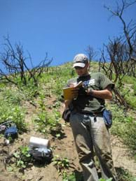 Photo shows a man standing on a dry hillside taking notes in a field book. Other equipment and materials are scattered nearby.