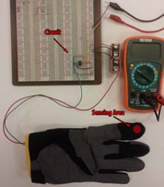 A photograph shows a top view of a multimeter attached via wires to a breadboard circuit that is attached via wires to a glove with a wired FlexiForce pressure sensor inside its index finger.