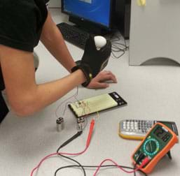 "A photograph shows a gloved hand—a student-designed tactile feedback system ""robotic hand""—applying pressure to an egg."" The glove is wired to a nearby breadboard and multimeter."