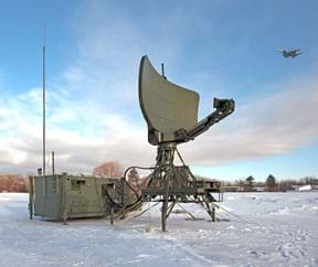 A photo shows an airplane flying over the Lockheed Martin TPS-79 mobile surveillance and air traffic control radar system, a 30-foot high piece of equipment mounted on tripod legs with an arc-shaped satellite dish panel.