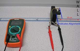 Photo shows a multimeter, measuring tape, and box to calibrate a Sharp GP2Y0A02YK0F Sensor. The sensor is facing the wall is connected to the multimeter by two wires, one red and one black with alligator clips.