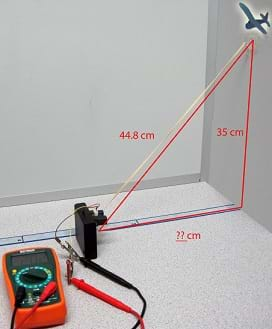 Photo shows a multimeter, airplane cutout, and Sharp GP2Y0A02YK0F sensor aimed at a wall. While the distance to the wall is unknown, the vertical distance along the wall to a clipart airplane is shown as 35 cm and the diagonal (slant range) distance from the clipart airplane to the sensor is shown as 44.8 cm.