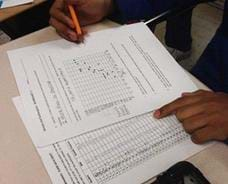 Photo shows a student at a table plotting points on a graph from data listed on a second sheet.